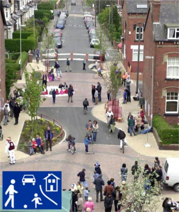Woonerf street in the UK, designed with narrow roadway, curves, trees, removable bollards, and physical barriers improve safety for pedestrians and ensure that motorist slow down. Colored pavement/texture also indicates pedestrian crossing zones. Photo Credit: Archinect.com